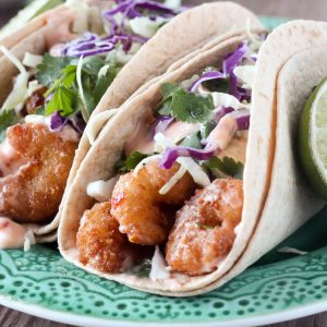 Crispy Sweet Chili Shrimp Tacos with Cilantro Slaw use popcorn shrimp to make an easy weeknight dish! Shrimp are topped with a creamy sweet chili sauce, and simple cilantro lime coleslaw.